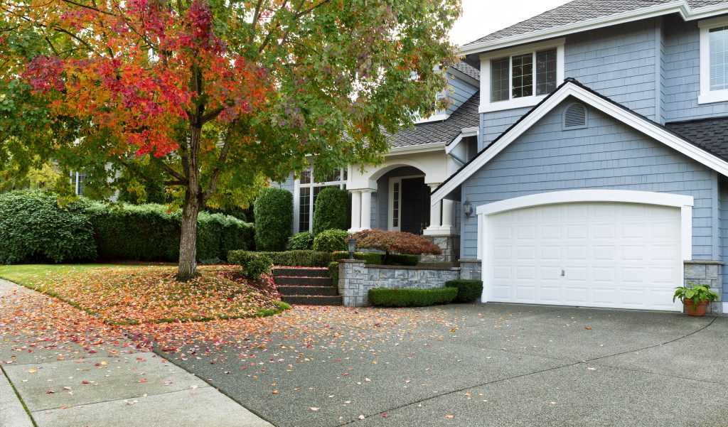 Front view of modern residential home during early autumn season in Northwest of United States. The garage door complements the rest of the house in a pleasing way. Maple trees beginning to change leaf colors.