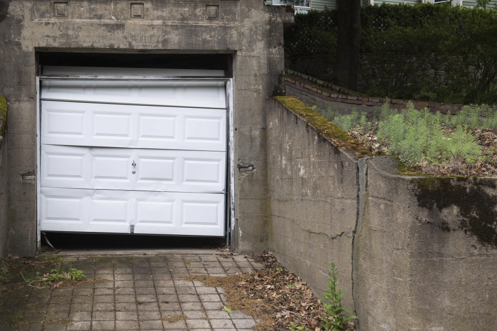 a white garage door that has many dents and it beat up.