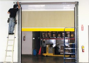 half closed brown garage door with someone working on the coil on a ladder.