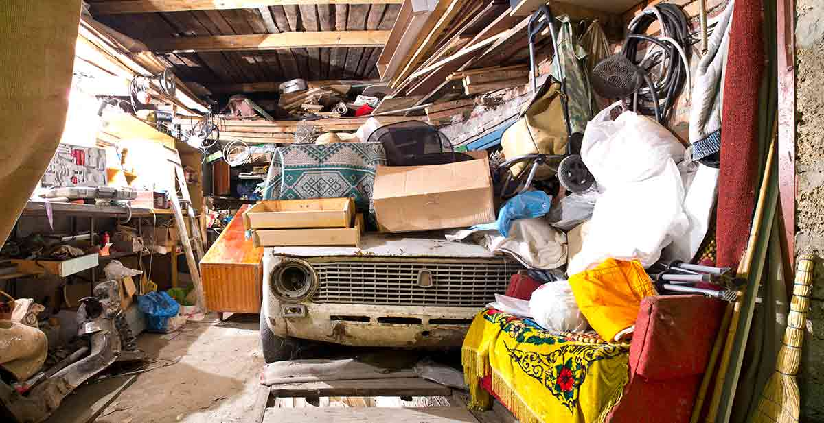 a dirty, cluttered garage with an old beat up car in it