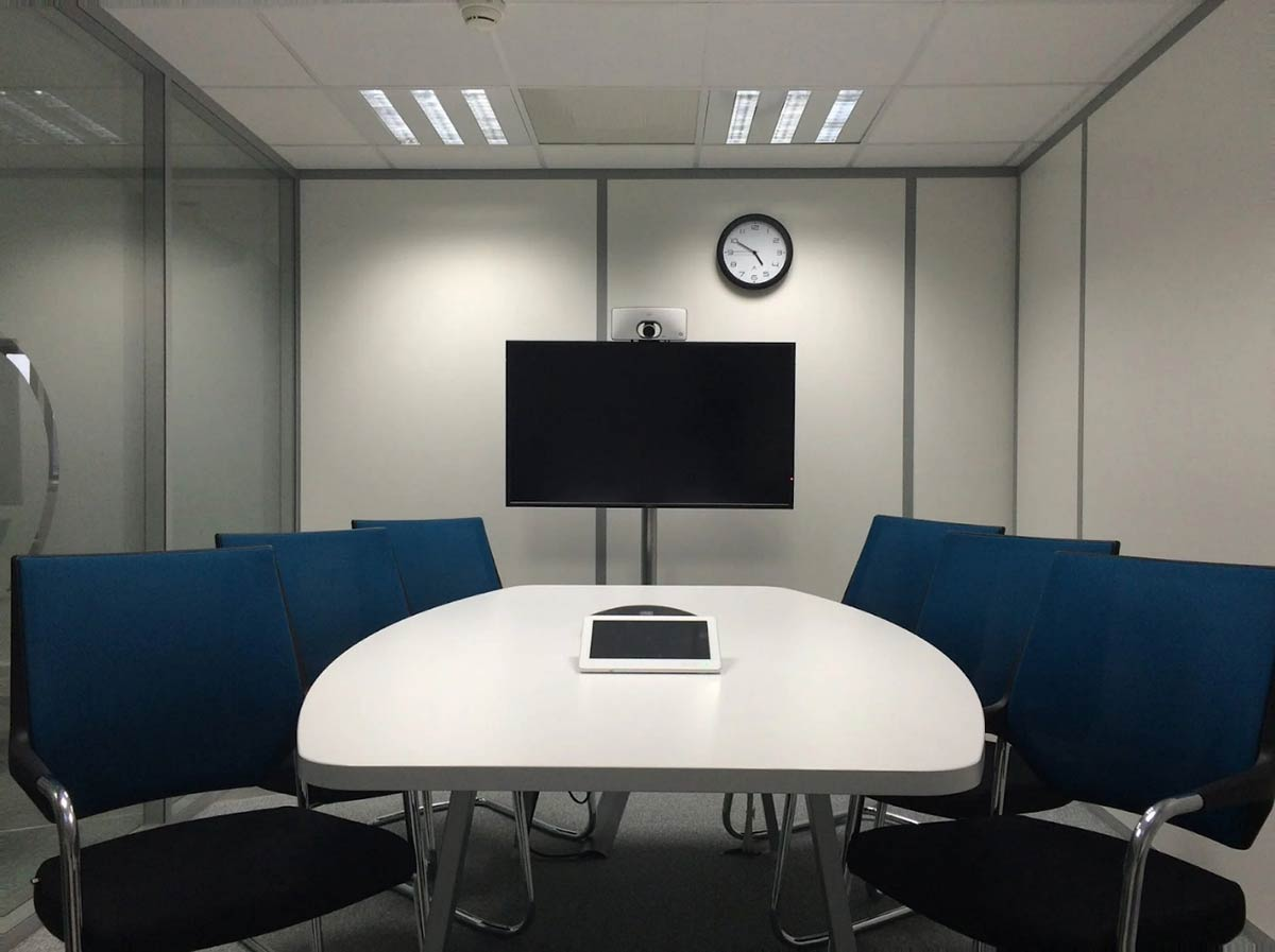 A folded partition wall being used to seclude a small meeting room at an office.