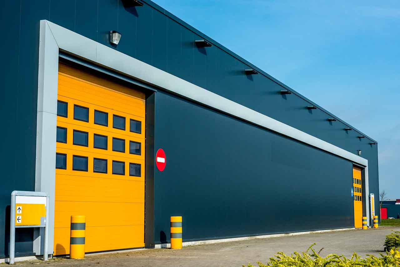 Modern yellow custom garage door with glass panels on a grey commercial building.