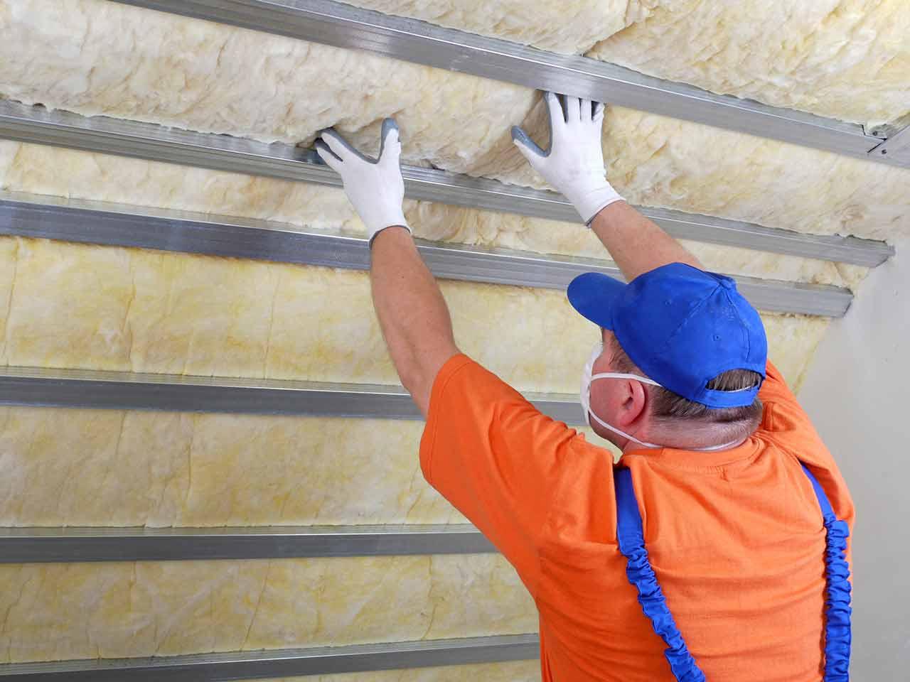 Picture of a man installing garage door insulation.