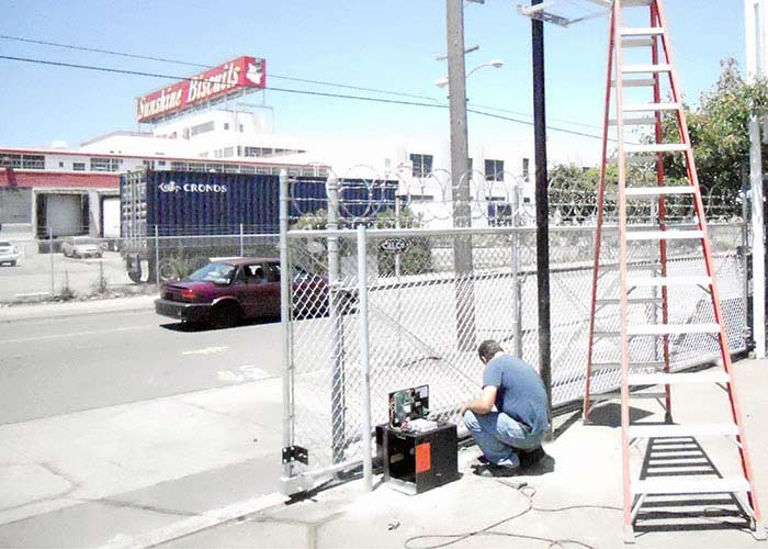 Repairman providing gate repair services by working on an automatic sliding gate